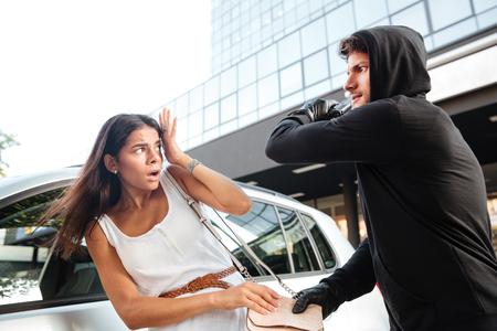 Hombre peligroso ladrón con pistola atacando a la joven asustada y robando su bolso Foto de archivo - 65857564