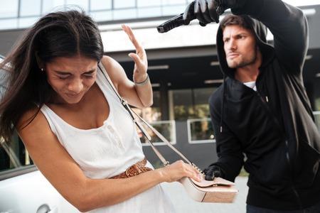 Hombre joven agresivo con el arma tratando de robar el bolso de la señora joven asustado en la calle Foto de archivo - 65833096