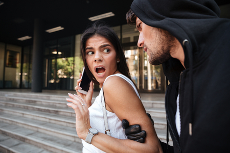 Frightened young woman with mobile phone shouting and being attacked by criminal man on the street Stock Photo