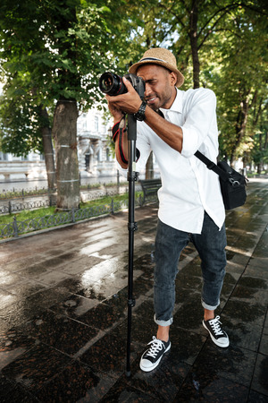 full lenght: Young black man in park. full lenght. with camera