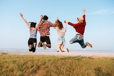 興奮して幸せな若者の手を押し、屋外空気中のジャンプの背面図