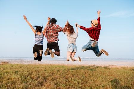relaciones humanas: Vista posterior de los jóvenes se interesen feliz la mano y saltando en el aire en el exterior