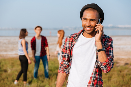 Cheerful african young man in hat standing near his friends and talking on cell phone 写真素材