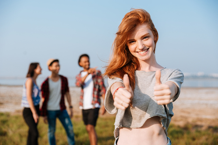 Cheerful redhead young woman standing and showing thumbs up while her friends talking outdoors