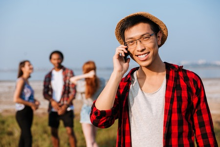 Smiling asian young man talking on cell phone standing near his friends outdoors