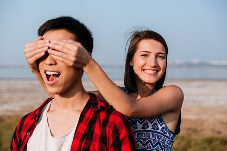 Happy cute young woman covered eyes by hands to her boyfriend outdoors Stock Photo - 130059371