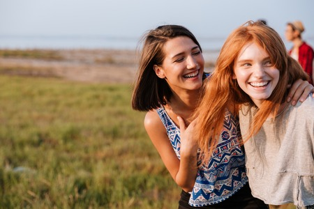 Two cheerful attractive young women laughing and having fun outdoors