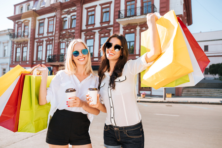 overspending: Two happy women holding shopping bags and having fun laughing in street Stock Photo