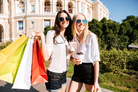 overspending: Two young fashion women with shopping bags having fun outdoors
