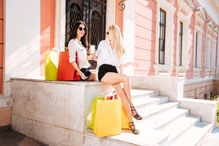 overspending: Two happy women with shopping bags sitting on steps
