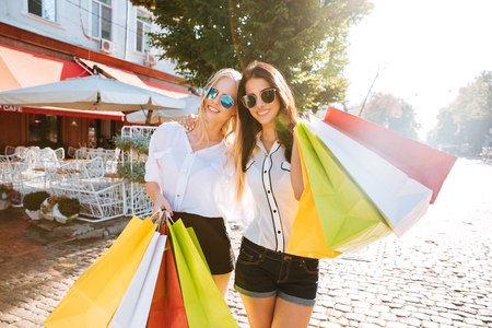 Two young fashion women with shopping bags walking along the street Stock Photo