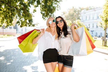 overspending: Two girls walking with shopping bags on city streets together Stock Photo