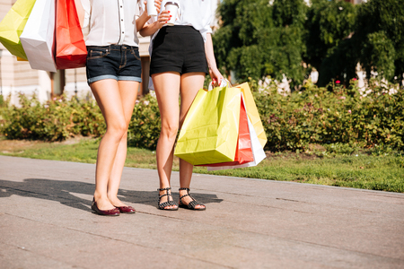 Cropped image of a two young female walking along street with shopping bags and coffee cups