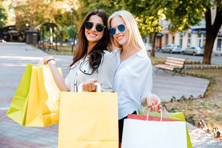 overspending: Stylish young ladies in sunglasses walking down the street with shopping bags Stock Photo