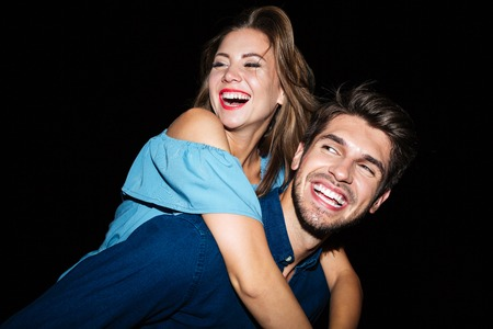 fling: Smiling attractive young man holding girlfriend on his back at night