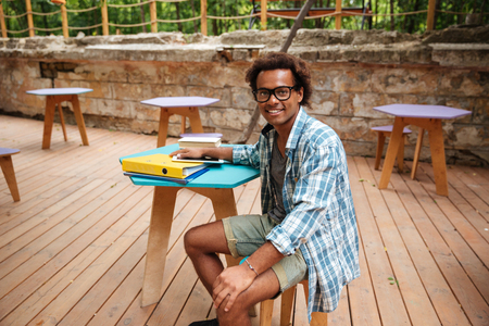 Cheerful young african man in glasses and plaid shirt sitting in outdoor cafe Stock Photo