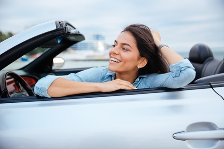 cabriolet: Cheerful smiling brunette woman resting in her cabriolet parked on the beach