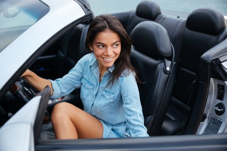 getting out: Smiling brunette young woman getting out of her convertible car