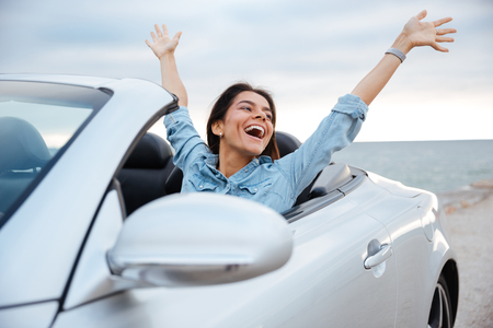 Young attractive brunette woman sitting with her hands up in cabriolet