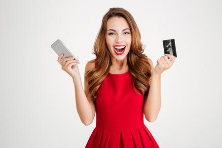 흰색 배경 위에 휴대 전화와 신용 카드와 쾌활한 흥분된 젊은 여자
