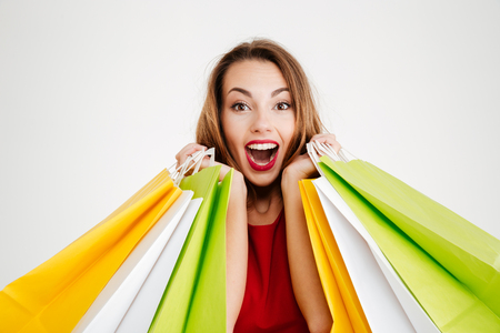 Close up portrait of a happy cheerful woman in red dress holding colorful shopping bags isolated on a white background Stock Photo