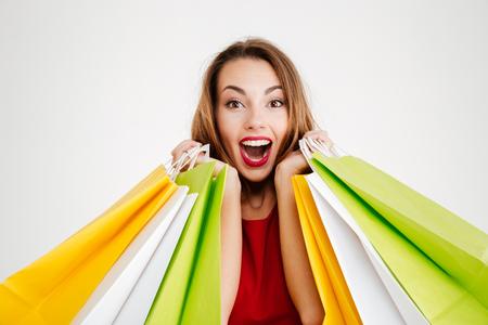 Feche acima do retrato de uma mulher alegre alegre no vestido vermelho segurando sacos de compras coloridos isolado em um fundo branco