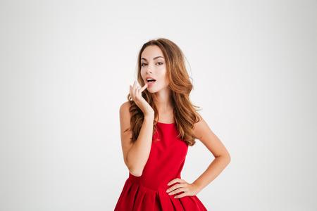 Retrato de una bella mujer lúdica en vestido rojo mirando a la cámara sobre fondo blanco