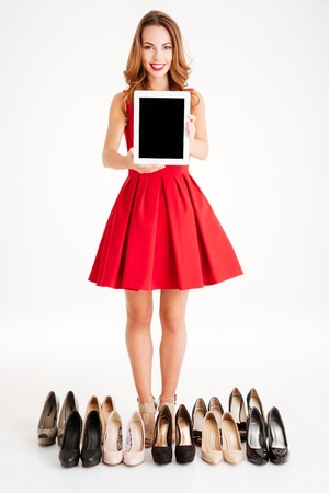 comprando zapatos: Retrato de una mujer joven y sonriente en traje rojo que sostiene la computadora y la compra de zapatos tableta de la pantalla en blanco aislado en un fondo blanco