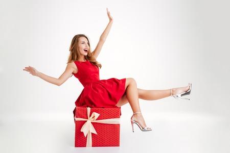 흰 배경에 고립 된 큰 선물 상자에 앉아있는 동안 재미 빨간 드레스에 쾌활 한 매력적인 여자 스톡 콘텐츠