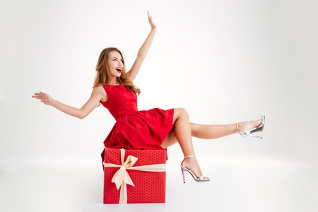 Cheerful attractive woman in red dress having fun while sitting on the big gift box isolated on a white background