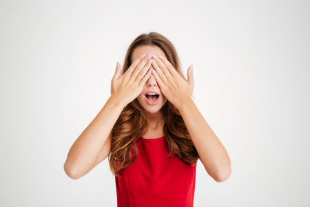 covering face: Portrait of a pretty lovely woman in red christmas dress covering face with palms over white background