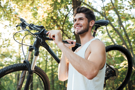 road shoulder: Cyclist holding bicycle in forest. side view Stock Photo