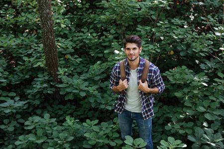 A partir de la imagen de hombre sonriente en el bosque. de la mano en el arnés