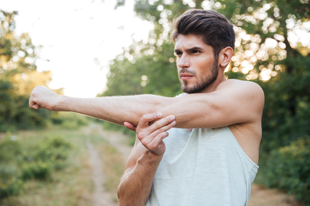 Runner warming up in forest. looking away. stretches hands Stock Photo