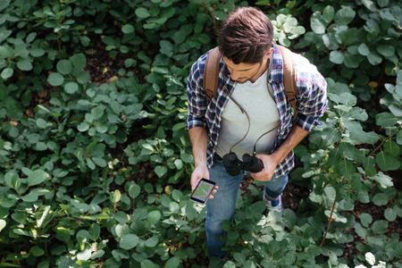 midst: From above image of guy in forest in the midst of plants. with binoculars and phone.