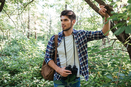 clinging: Young man with backpack near the tree looking away. man in shirt with binoculars