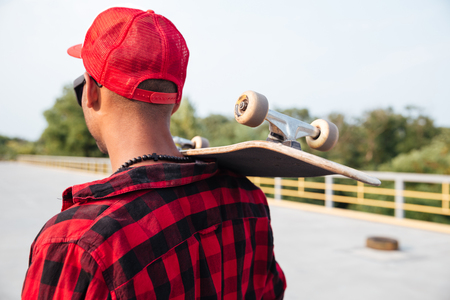 Picture of young dark skinned guy holding skateboard. Against the nature background. Stock Photo