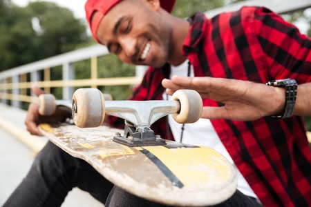 Picture of happy dark skinned guy wearing cap looking on his skateboard. Against nature background.