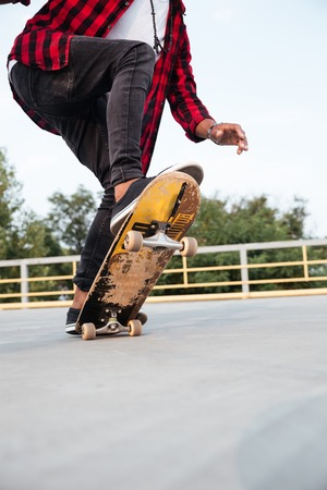 Photo of young dark skinned guy skateboarding. Against the nature background. Stock Photo