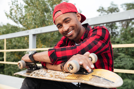 Photo of cheerful dark skinned man wearing cap holding skateboard. Against nature background. Looking at the camera.
