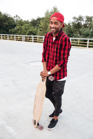 Picture of young cheerful dark skinned man wearing cap holding his skateboard. Against the nature background.