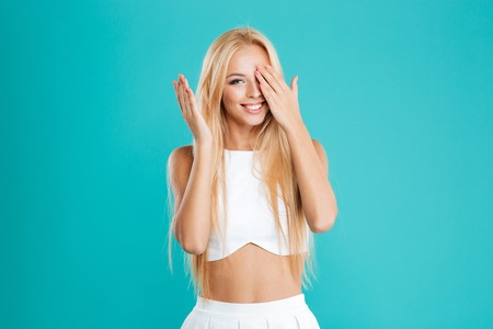 Portrait of a cheerful young woman standing and covering eye with her palm isolated on the blue background Stock Photo