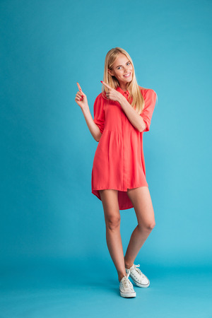 Full length of smiling pretty young woman standing and pointing two fingers up isolated on a blue background