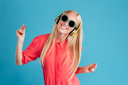 Portrait of a smiling cheerful blonde woman in sunglasses listening music with headphones and dancing over blue background