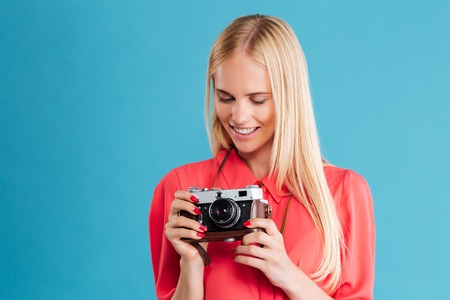 Portrait of a pretty casual blonde girl with retro camera over blue background Stock Photo