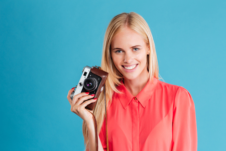 Portrait of a charming smiling woman holding retro camera over blue background Foto de archivo