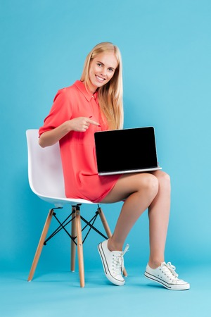 Full length portarit of a smiling blonde girl pointing at blank screen laptop while sitting on chair isolated on the blue background Stock Photo