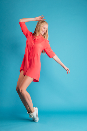 Full length portrait of a blonde happy woman posing on her tiptoes isolated on a blue background