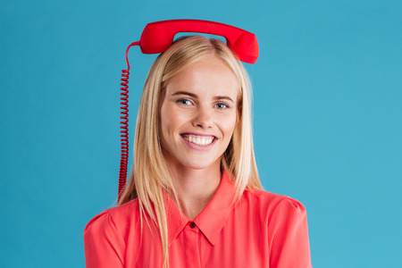 red tube: Close up portrait of a smiling happy blonde woman with red tube on her head isolated on a blue background