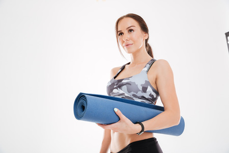 Fitness woman with mat. looking away. isolated white background
